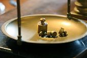 picture of gold panning  - ancient brass precision scales with weights above the ancient balance Pan