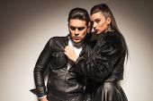 pic of jacket  - Side view of a gorgeous fashion woman pulling her lovers leather jacket while he is looking down - JPG
