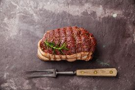 picture of slating  - Raw roast beef Rump and meat fork on dark stone slate background - JPG