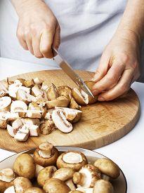 stock photo of crimini mushroom  - Chef cutting the mushrooms on a wooden board - JPG