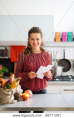 Happy Woman With Shopping List And Bag Of Fresh Produce