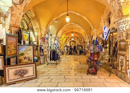 JERUSALEM, ISRAEL - JULY 16, 2015: Gift shops inside of stone vault passage in Old City of Jerusalem - one of the oldest cities in the world and holy in Judaism, Islam and Christianity.
