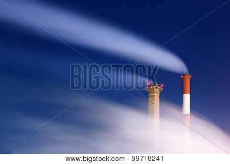 Smoking tall factory chimneys at night