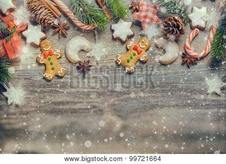 Christmas decoration with gingerbread cookies,fir branches and spices on the old wooden board. Vintage style. Old film grain effect.