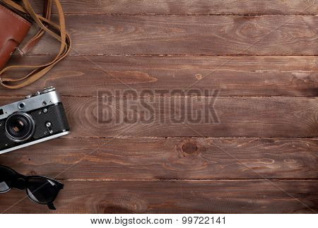 Camera and sunglasses on wooden desk table. Top view with copy space