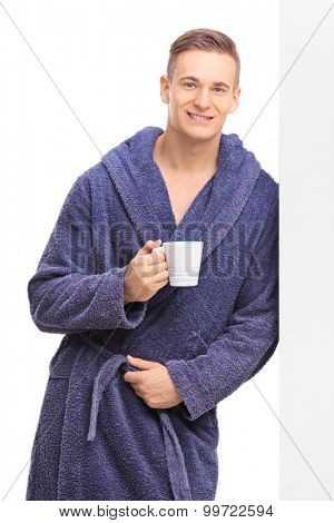 Vertical shot of a young man in a blue bathrobe holding a cup of coffee and leaning against a wall isolated on white background
