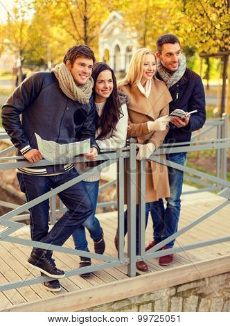 travel, people, tourism, and friendship concept - group of smiling friends with map and city guide standing on bridge in city park