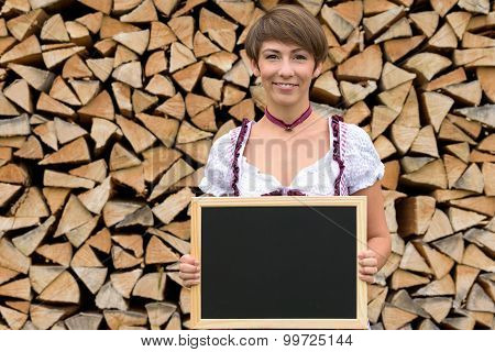 Young Woman In A Dirndl Holding A Blank Slate