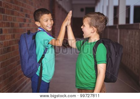 Pupils giving each other a high five on the elementary school grounds
