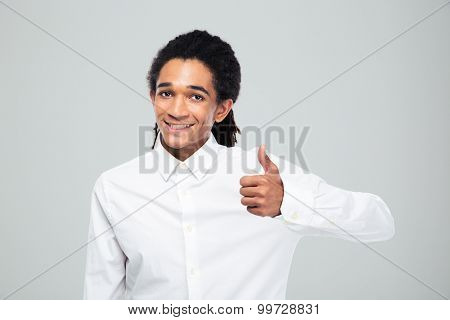 Happy afro american businessman showing thumb up over gray background