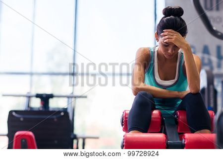Tired sports woman sitting on exercises machine in fitness gym