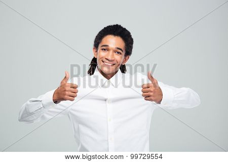 Cheerful afro american businessman showing thumbs up over gray background