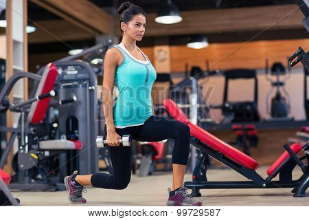 Full length portrait of a young woman workout with dumbbells in fitness gym