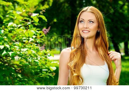 Portrait of a beautiful young woman smiling to a sunny summer day. She is absolutely happy. Beauty, fashion.