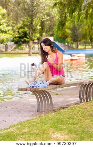 Brunette model wearing pink top and white shorts relaxing in park environment, sitting on bench next