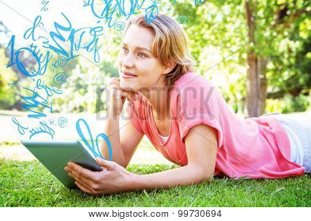 Letters numbers and punctuation against pretty woman using tablet in park