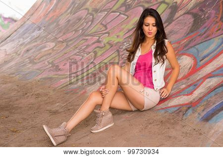 Brunette model wearing pink top, white vest and shorts sitting down on concrete skatepark surface wi