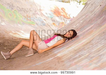 Brunette model wearing pink top, white vest and shorts lying down on concrete skatepark surface with