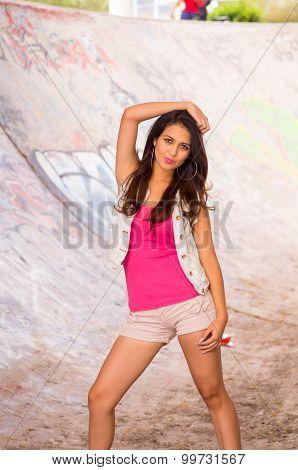Brunette model wearing pink top, white vest and shorts standing inside concrete skatepark posing for