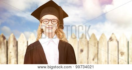 Cute pupil in graduation robe against fence under blue sky