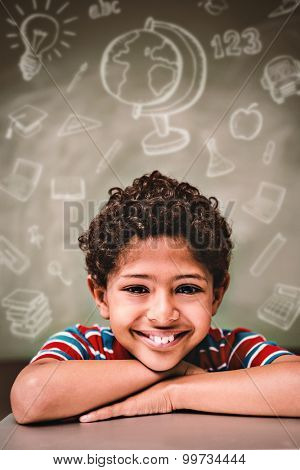 Education doodles against little boy smiling in classroom