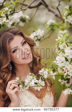 Young beautiful brunette woman in blooming garden.