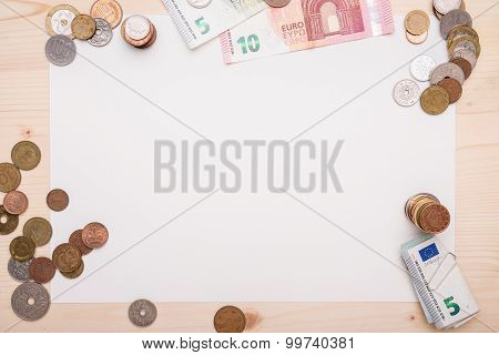 Different Coins, Arranged Around A White Piece Of Paper