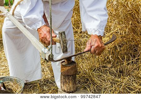 Farmer Is Sharpening, Ironing, Repair The Blade On Scythe.