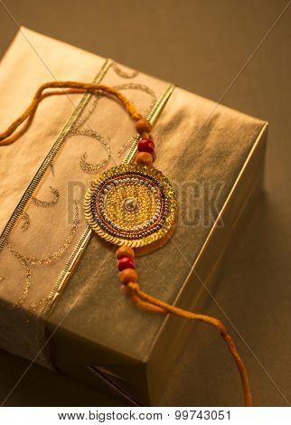 A golden gift pack with Rakhi string,