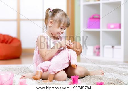 girl playing with her baby-doll
