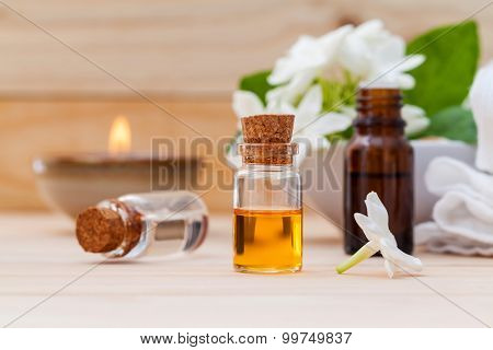 Aroma Oil Bottles Arranged With Jasmine Flowers On Wooden Background .