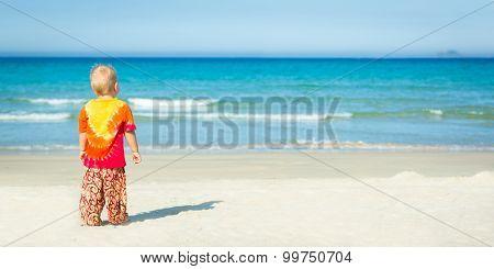 Baby looking sea on the beach. Panorama