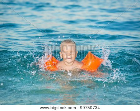 Baby with armbands in a sea