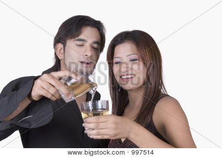 Close-Up Of A Young Man Pouring White Wine Into A Young Woman'S Wine Glass