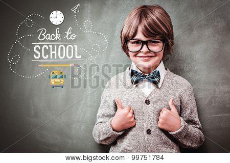 back to school against little boy gesturing thumbs up against blackboard
