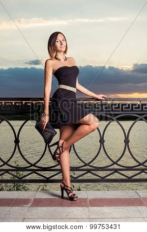 Fashion girl with is standing on one leg with her handbag