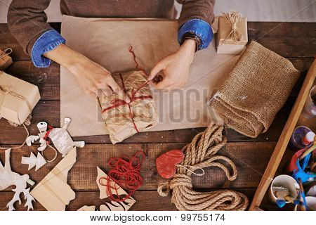 Male hands tying up wrapped gift with red woolen thread