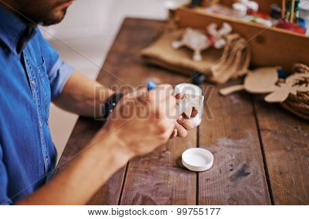 Man painting wooden firtree with white gouache