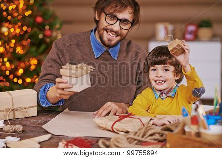Happy young man and little boy with giftboxes looking at camera