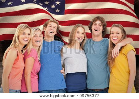 A group of friends holding each other and smiling against composite image of digitally generated united states national flag