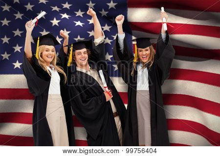 Three students in graduate robe raising their arms against digitally generated american national flag