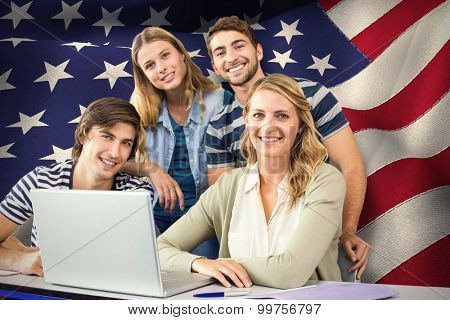 Students using laptop in classroom against digitally generated american national flag