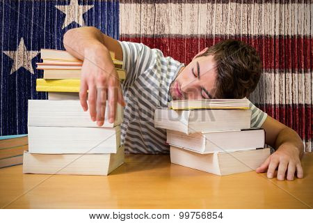 Student asleep in the library against composite image of usa national flag