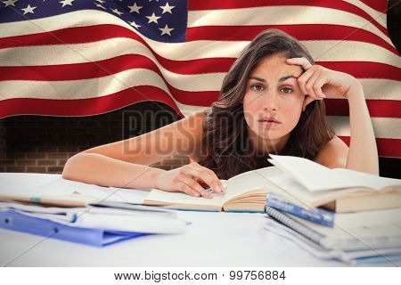 Bored student doing her homework against composite image of digitally generated united states national flag