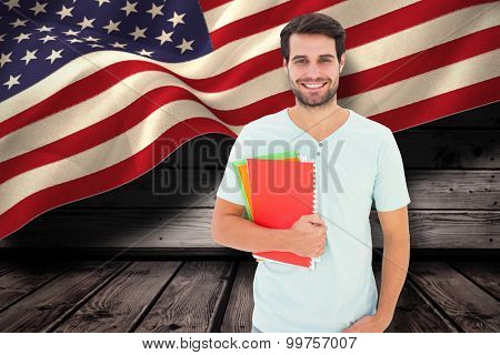 Student holding notepad against composite image of digitally generated united states national flag