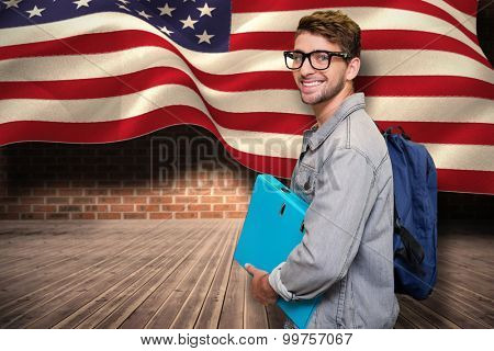 Student smiling at camera in library against composite image of digitally generated united states national flag