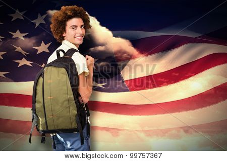 Casual young man in office corridor against composite image of digitally generated american flag rippling