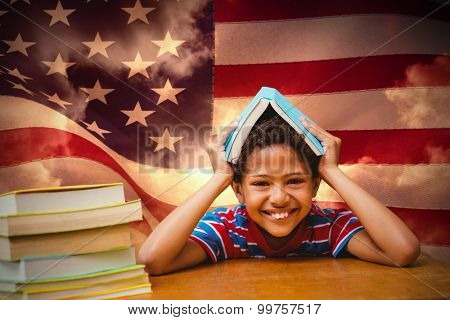 Pupil with many books against composite image of digitally generated united states national flag