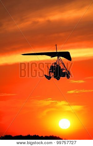 Hang-glider Flying In The Light Of The Setting Sun.