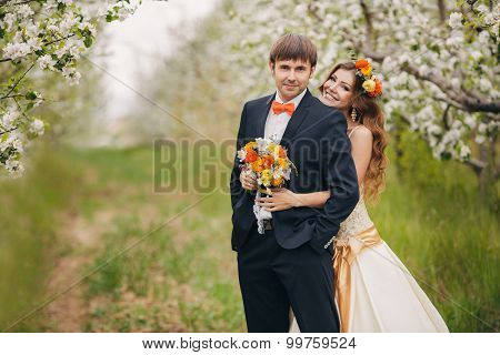 Bride and groom in the lush spring garden